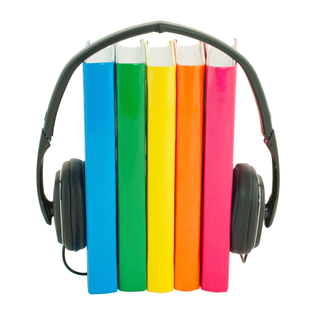 Row of books and headphones isolated over white